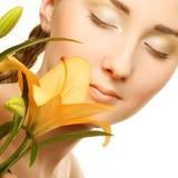 Visage de femme de beauté avec la fleur jaune de lis Image stock