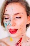 Visage de femme en peinture faisant la langue  photographie stock libre de droits
