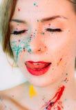 Visage de femme en peinture faisant la langue, lèvres rouges images stock