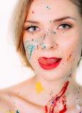 Visage de femme en peinture faisant la langue, lèvres rouges photographie stock libre de droits