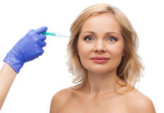 Visage de femme et main heureux d'esthéticien avec la seringue Image stock