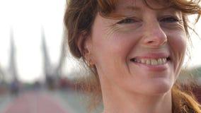 Visage de femme supérieure rousse avec le sourire de taches de rousseur banque de vidéos