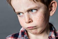 Visage de garçon triste avec les yeux bleus pleurants pour la colère Image stock