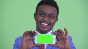 Visage de jeune téléphone africain heureux d'apparence d'homme d'affaires banque de vidéos