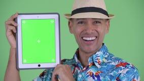 Visage de l'homme de touristes ethnique multi heureux montrant le comprimé numérique et semblant étonné banque de vidéos