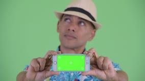 Visage de l'homme de touristes ethnique multi heureux pensant tout en montrant le téléphone banque de vidéos