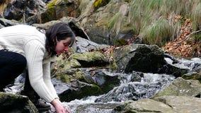 Visage de lavage de belle femme avec la rivière de montagne d'eau propre banque de vidéos