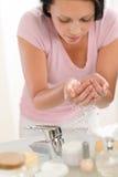 Visage de lavage de femme avec de l'eau dans la salle de bains photographie stock libre de droits