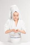 Visage de nettoyage de femme dans la salle de bains image libre de droits
