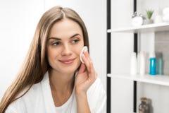 Visage de nettoyage de femme avec la protection de coton images stock