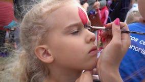 Visage de peinture de peu de fille mignonne d'enfant avec les cheveux bouclés blonds Mouvement de cardan clips vidéos