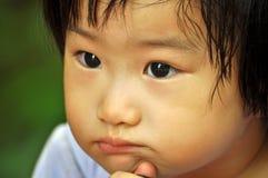 Visage de petits enfants asiatiques ennuyés Image stock