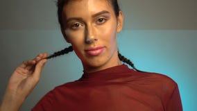 Visage de plan rapproché de jeune femme attirante posant à l'appareil-photo dans le studio banque de vidéos