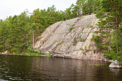 Visage de roche à un lac Photos stock