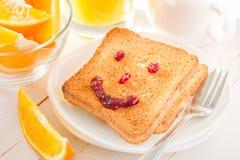 Visage de sourire avec la confiture sur le pain grillé Image stock