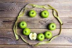 Visage de sourire des pommes vertes et de la bande jaune de centimètre sur vieux W Images libres de droits