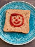 Visage de sourire heureux sur un pain grillé Photographie stock libre de droits