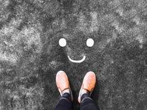 Visage de sourire sur la route et le fond rose de chaussure d'espadrille photo stock