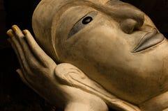 Visage de statue de Bouddha reposant en main Images stock