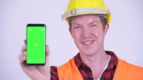 Visage de téléphone heureux d'apparence de travailleur de la construction de jeune homme banque de vidéos