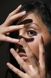 Visage derrière des doigts Photographie stock
