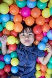Visage des enfants asiatiques dans la piscine colorée de boule image libre de droits
