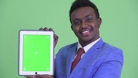 Visage du jeune homme d'affaires africain heureux montrant le comprimé numérique banque de vidéos