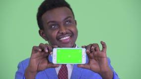 Visage du jeune homme d'affaires africain heureux pensant tout en montrant le téléphone banque de vidéos