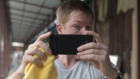 Visage du jeune homme de touristes essuyant la sueur et à l'aide du téléphone comme miroir au pilier local à Bangkok banque de vidéos