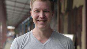 Visage du jeune homme de touristes heureux souriant au pilier local à Bangkok banque de vidéos