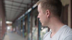 Visage du jeune homme de touristes souriant et pensant au pilier local à Bangkok banque de vidéos