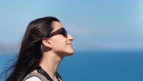 Visage en gros plan de voyageuse agréable de femme dans des lunettes de soleil jouant avec des cheveux au fond de ciel de mer banque de vidéos