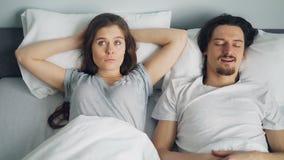 Visage fâché de bâche d'épouse avec l'oreiller tandis que mari de sommeil ronflant dans le lit banque de vidéos
