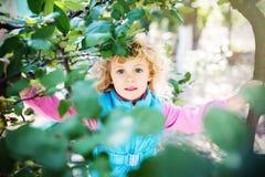 Visage heureux d'enfant entre les feuilles Photos stock