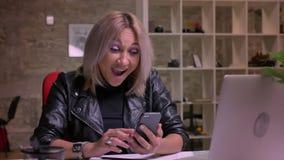 Visage heureux riant de la fille caucasienne blonde qui s'assied au lieu de travail et à mettre en rouleau son téléphone, ordinat clips vidéos