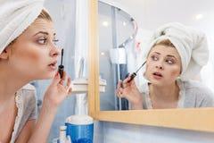 Woman in bathroom applying mascara on eyelashes Stock Photos