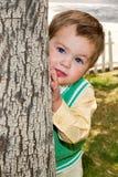 Visage malpropre bien habillé de garçon derrière l'arbre Photo stock