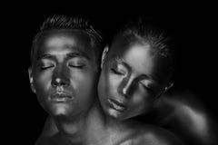 Visage masculin et femelle autour La tête du ` s de femme se trouve sur l'épaule d'un homme Tous peints en peinture d'or, le sent Images stock