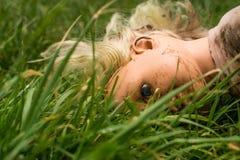 Visage menteur de poupée en plastique vers le bas dans l'herbe Photo libre de droits
