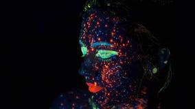 visage peint avec la lueur dans la peinture fonc?e Femme de mannequin dans les lampes au néon posant dans le studio, portrait de  banque de vidéos
