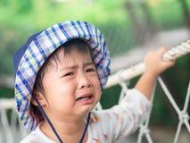 Visage pleurant triste de petite fille sur le fond de bokeh avec le fil de vintage photographie stock
