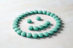Visage souriant des pilules sur la table en bois Photo libre de droits