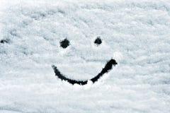Visage souriant dessiné sur la neige Image libre de droits