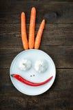 Visage souriant fait à partir du poivre, de l'ail, de l'assaisonnement et des carottes Photos libres de droits