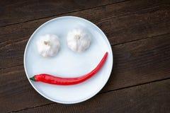 Visage souriant fait à partir du poivre et de l'ail Photographie stock