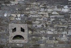 Visage triste sur le mur de briques Photo libre de droits