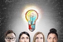 Visages d'équipe d'affaires, ampoule, tableau noir Photo stock