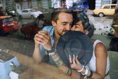 Visages de dissimulation de couples mignons derrière le chapeau en café Images libres de droits
