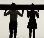 Visages de dissimulation de jeunes couples derrière le conseil Images libres de droits