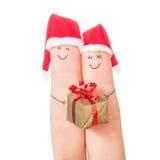 Visages de doigts dans des chapeaux de Santa avec le boîte-cadeau Image stock